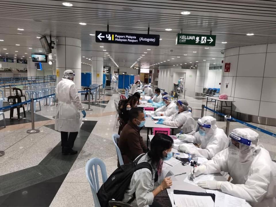 Returning individuals getting screened by health officials at Kuala Lumpur International Airport.