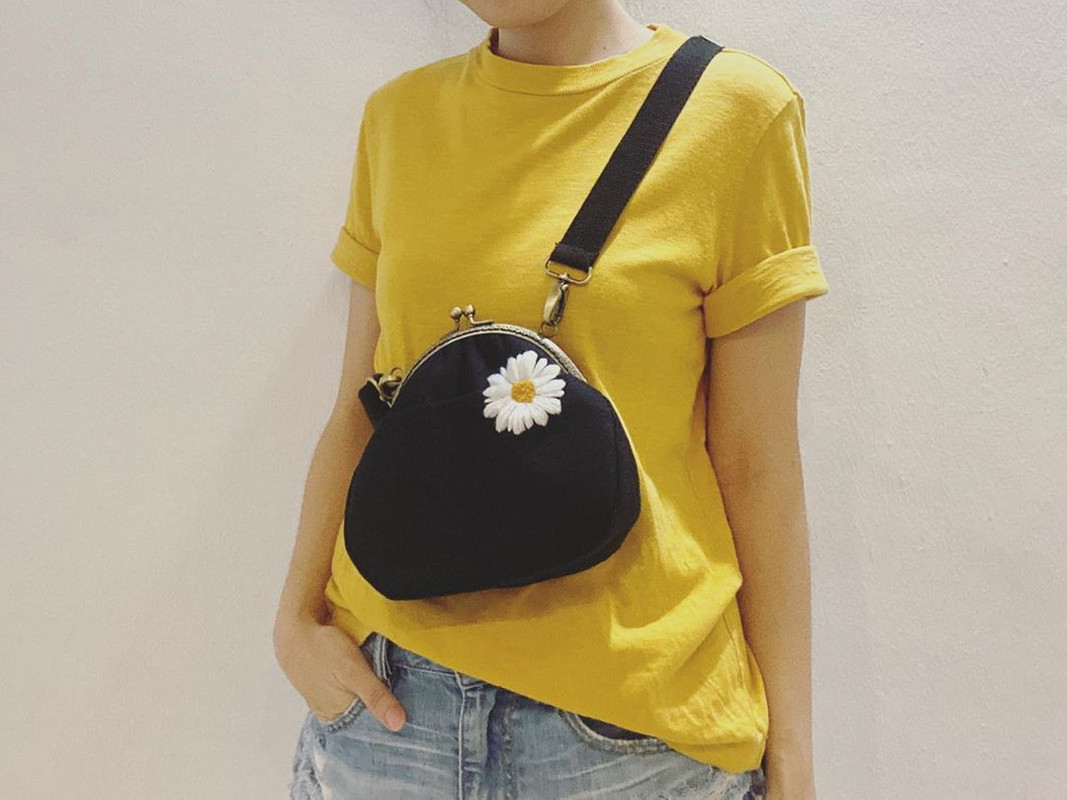 A black sling bag with an embroidered daisy.