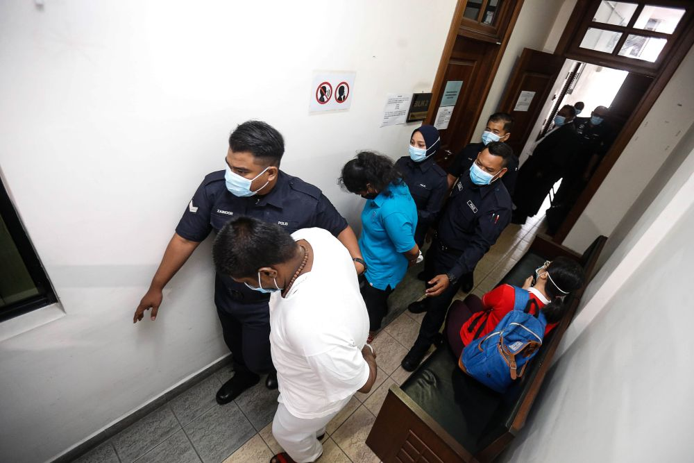 Gayathry (in blue) and Saravanan (in white) pictured at the Penang High Court in George Town.
