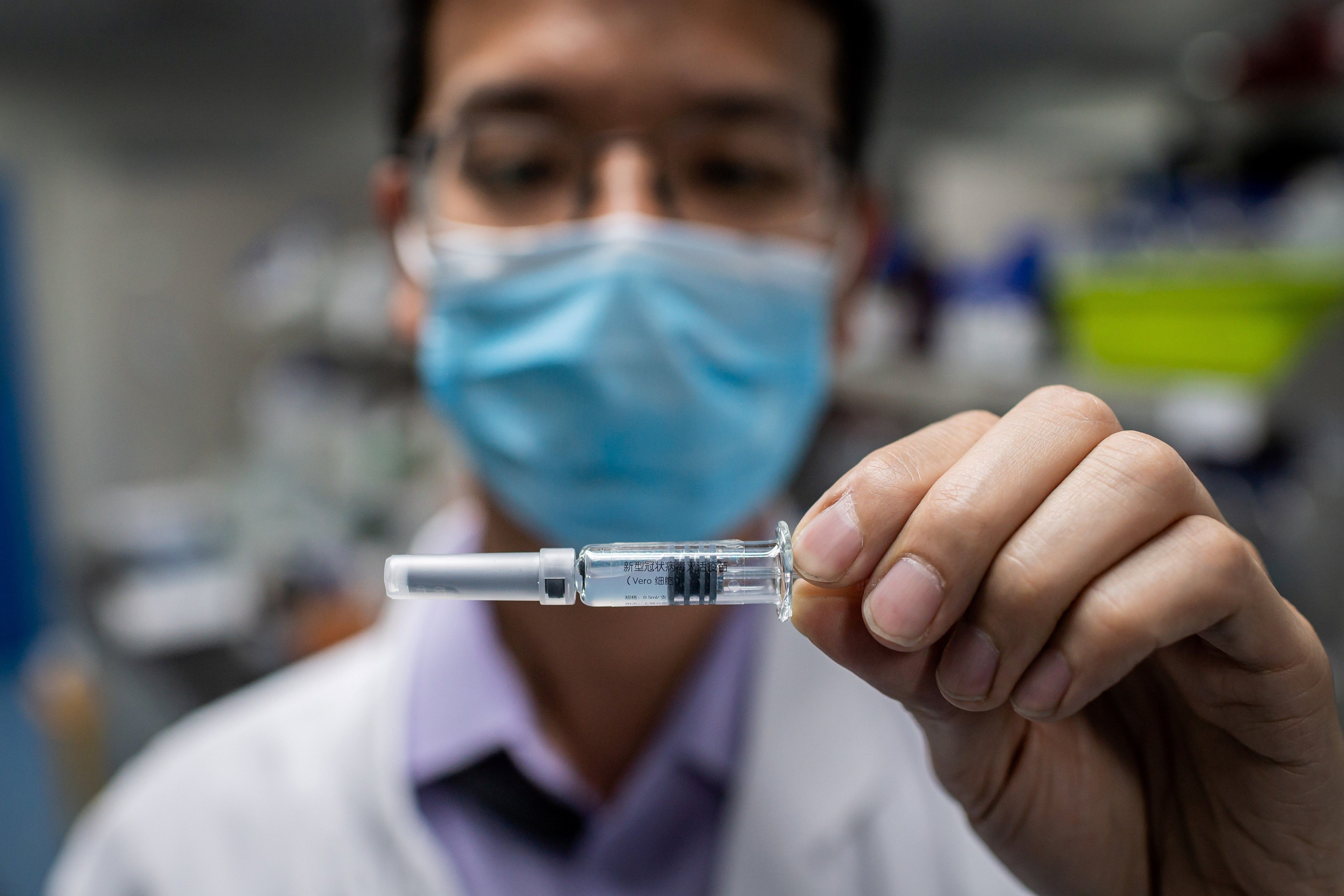 An engineer shows a COVID-19 vaccine candidate in Beijing.