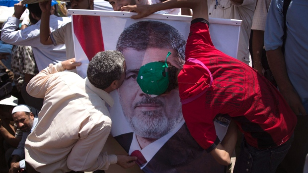Egyptian men kiss a picture of President Mohammed Morsi rally in Cairo, Egypt, Friday, June 21, 2013.