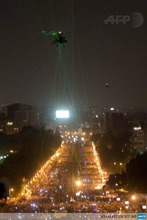 Egyptian protestors direct laser lights on a military helicopter flying over the presidential palace in Cairo. Image from AFP.