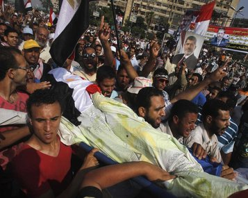 Morsi's supporters carrying one of the victims killed in the attack in Cairo yesterday.