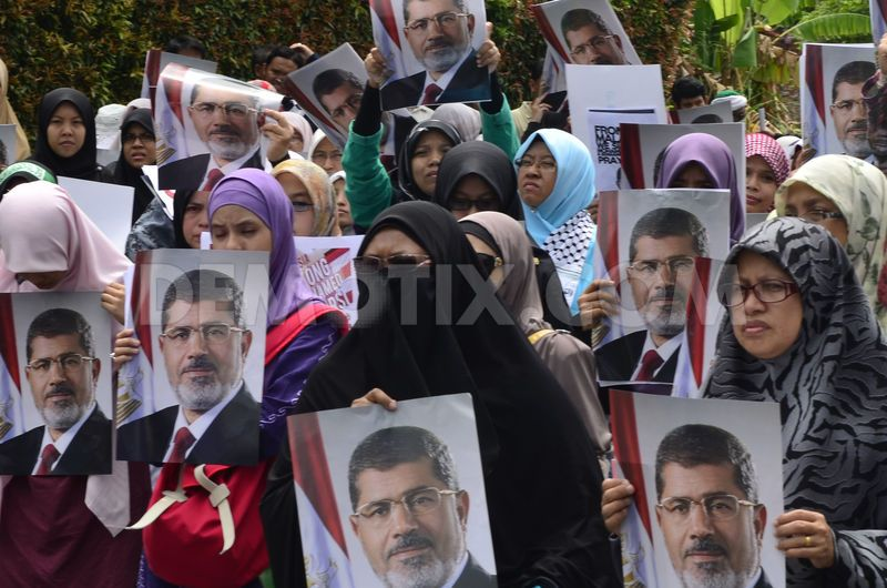 Malaysian Islamist protesters hold posters of ousted Egyptian President Mohammed Morsi during a protest to oppose the military overthrow of the Islamist leader and subsequent killings in Egypt, outside the Egyptian embassy in Kuala Lumpur.