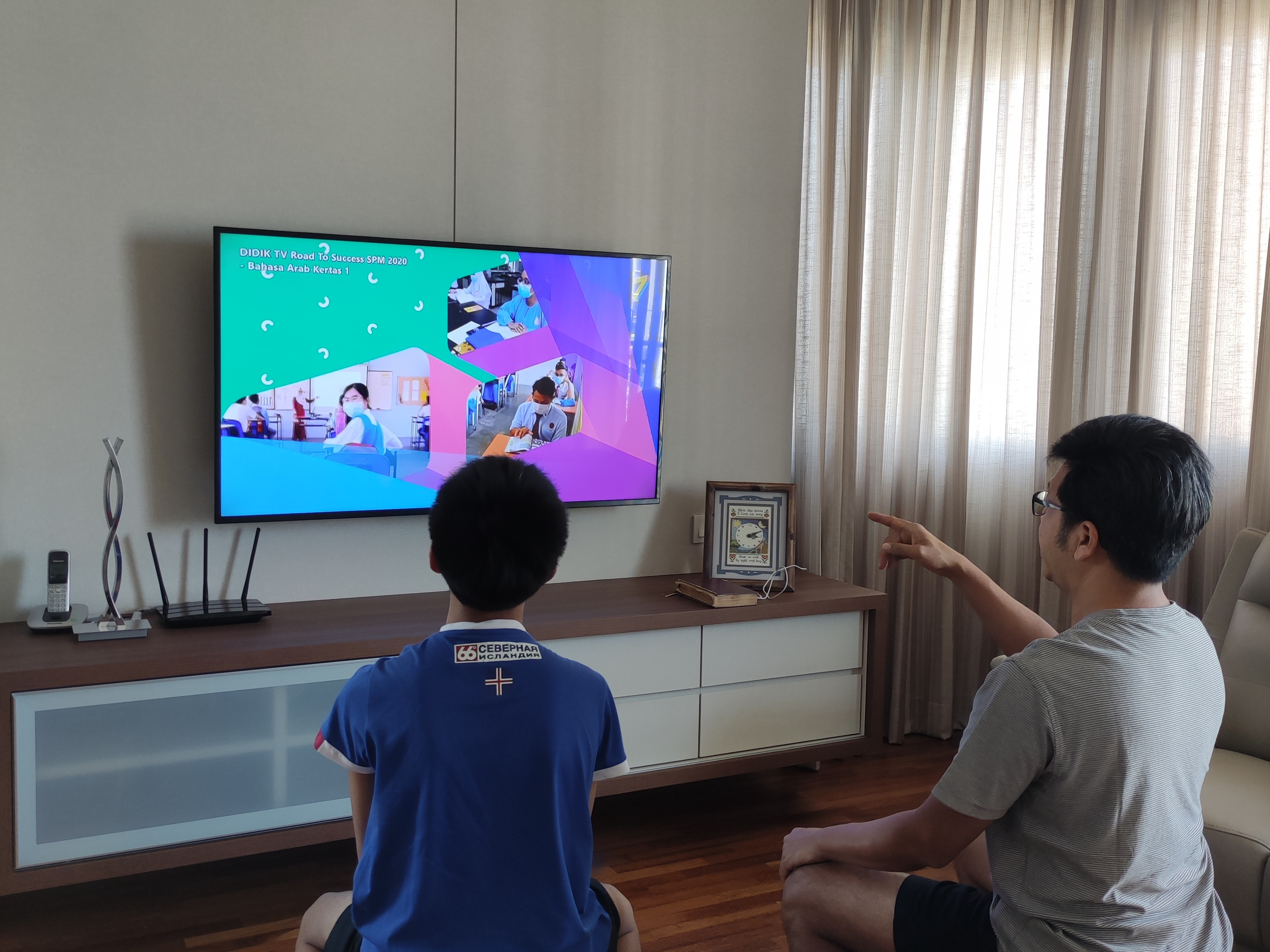 Ng Kok Chee watching DidikTV with his 13-year-old son.