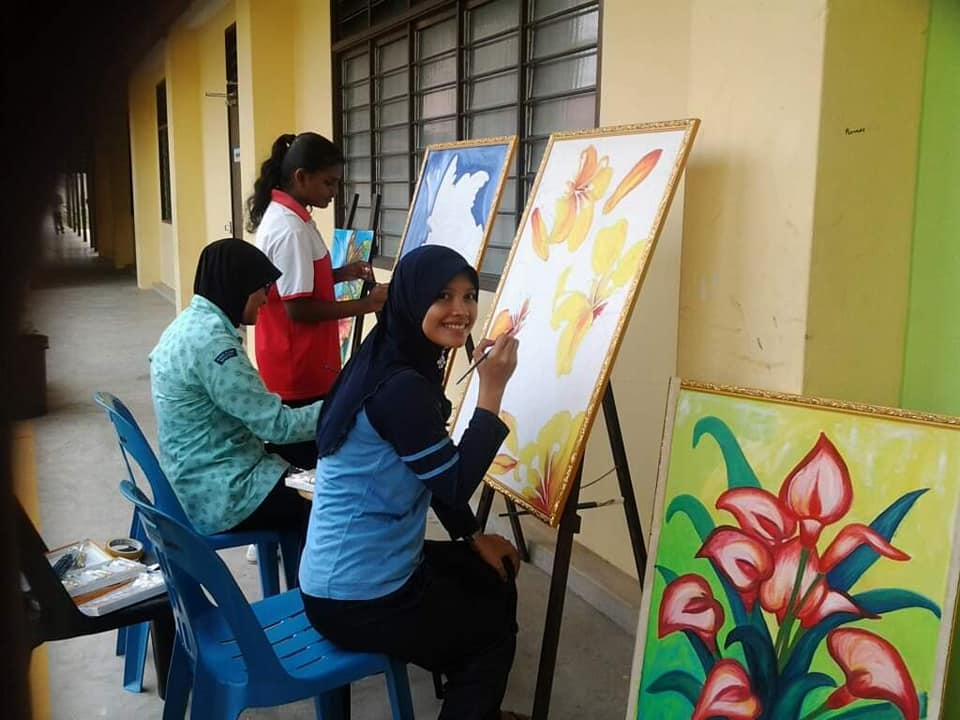Cikgu Jue teaching students how to paint on easels