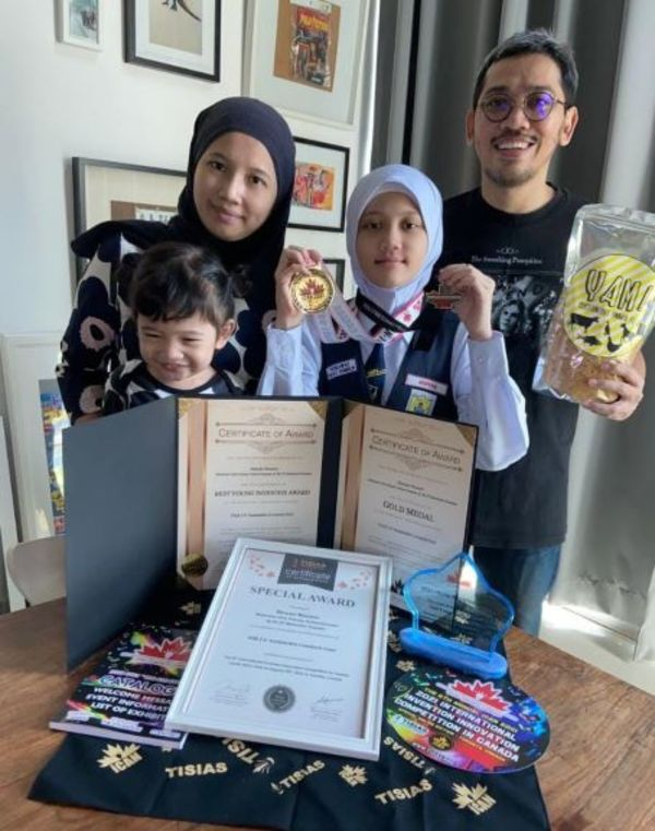 Maryam Muzamir with her family showing the medals and certificates she won at iCAN 2021 on 28 August.